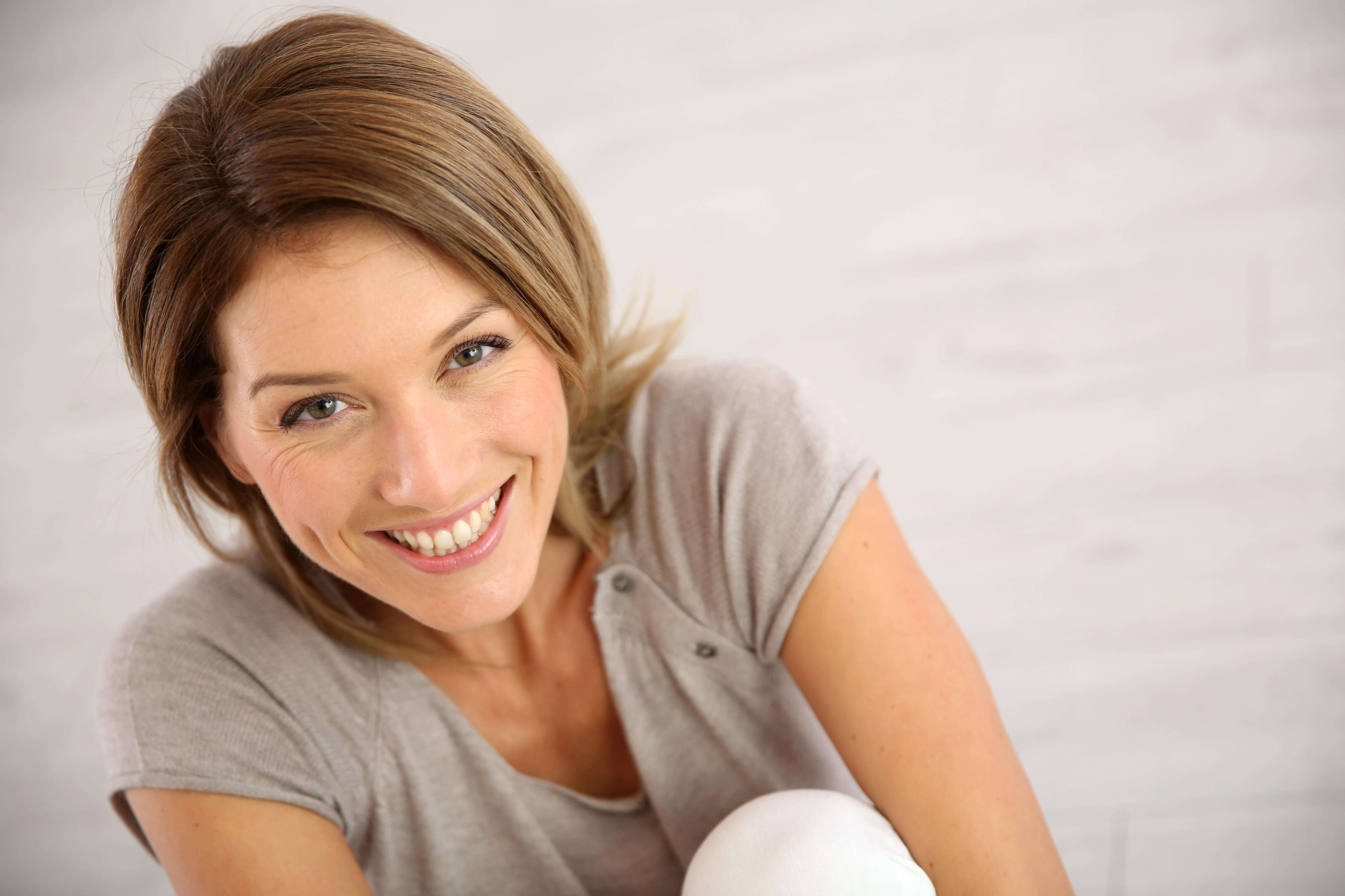 Portrait of woman smiling over shoulder - Stock Photo