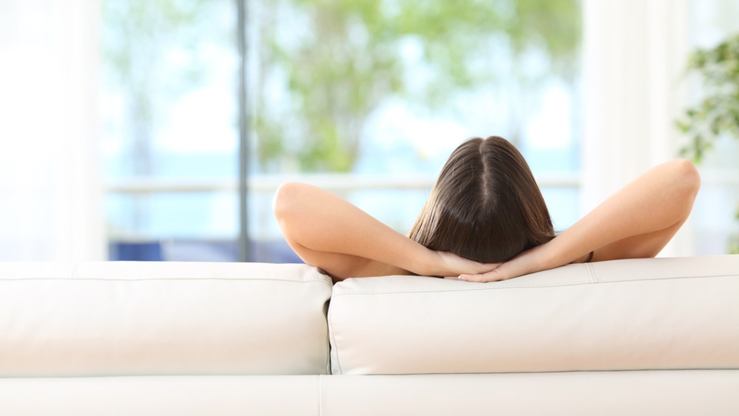 Rear view of a woman relaxing sitting on a couch with the hands on the head and looking outdoors through the window of the livingroom at home; Shutterstock ID 417115363; PO: today.com