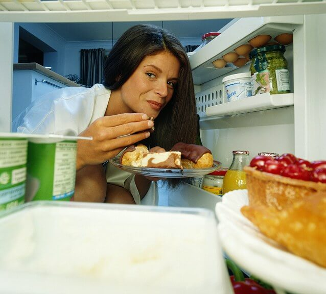Woman taking cream cakes out of fridge, view from inside fridge