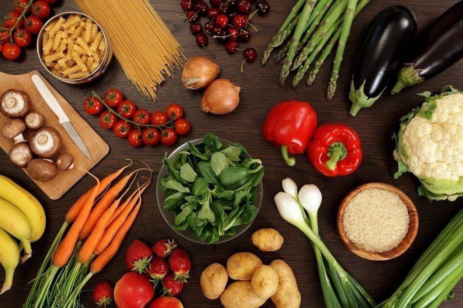 Photo of a table top full of fresh vegetables, fruit, and other healthy foods.