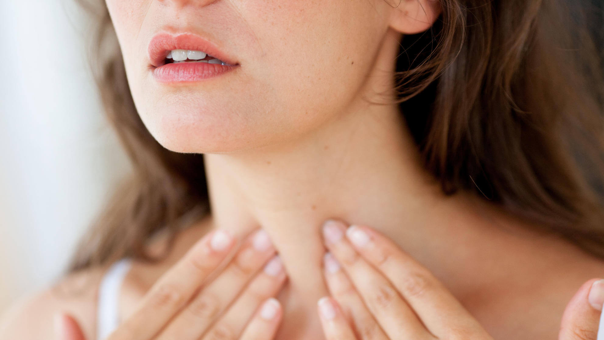 Woman self-examining her throat.