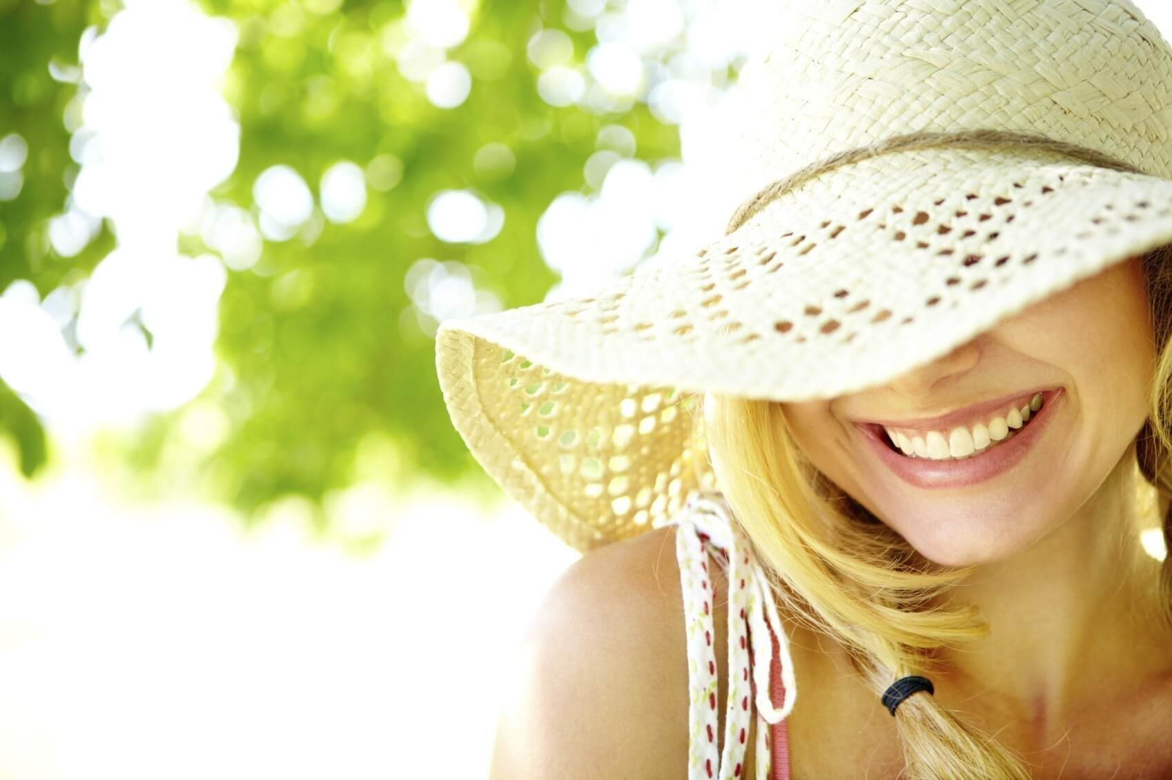 Smiling blonde with hat covering eyes with copyspace